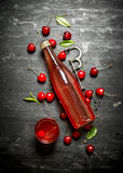 Bottle of fresh cherry juice with the leaves around. Royalty Free Stock Photos
