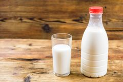 Bottle of fresh farm milk with red lid and glass of milk on wooden background. Side view. Stock Photos