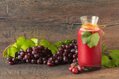 A bottle with fresh grape juice. On rustic wooden table royalty free stock photo