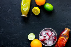 Bottle of fresh lemonade, fruits and ice cubes on black stone background top view copyspace Royalty Free Stock Photos