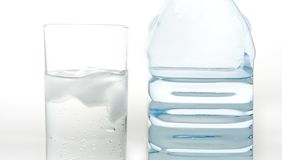 A bottle of fresh mineral water and a glass Stock Photos