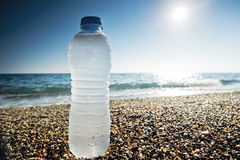 Bottle of fresh water is on the sand Stock Images