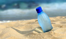 Bottle of the fresh water on sand Stock Images