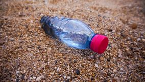 Plastic bottle in the sand. Bottle of fresh water on the sand royalty free stock photos