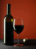 Bottle and glass. Still-life with wine bottle and glass over red background stock photos