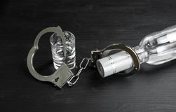 Bottle and glass with alcohol drink and handcuffs on black wooden table. Alcohol dependence.  royalty free stock photo