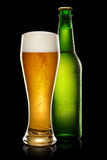 Bottle and glass of beer. Green wet Bottle of beer and glass of beer on black background Stock Photo