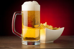 Bottle, glass of beer and potatoe chips on stone table over red Royalty Free Stock Photos