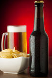 Bottle, glass of beer and potatoe chips on stone table over red Stock Image