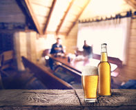 Bottle and glass of beer on table Stock Photos