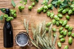 Bottle and glass beer with wheat and hops as brewing ingredients in top view and copy space area. Flat lay. Still life Royalty Free Stock Images