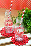 Bottle glass. Bottles and red striped paper straws Royalty Free Stock Photography
