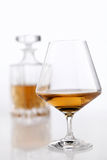 Bottle and glass of brandy on a white table Stock Images