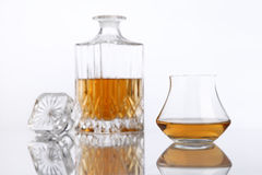 Bottle and glass of brandy on a white table Stock Photography