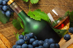 Bottle, glass of cognac and bunch of grapes. Still life with bottle, glass of cognac and bunch of grapes Royalty Free Stock Photography