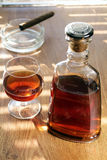 Bottle and glass with cognac and cigar Stock Photography