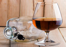 Bottle and glass. Empty bottle and half filled glass with cognac on a background from boards Stock Image