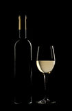 Bottle and glass of fine white wine. Isolated on black background Stock Images