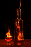 Bottle and glass in flame Royalty Free Stock Images
