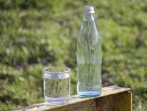 Bottle and glass with fresh  water on grass  background. royalty free stock photography