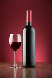 Bottle and glass full of red wine over a red backdrop Royalty Free Stock Images
