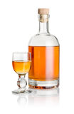 Bottle and glass goblet filled with amber liquid Stock Photo
