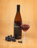 Bottle, glass and grapes on wooden background Stock Images