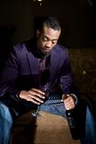 The bottle, the glass and the hesitation. A fashionable, youthful african american contemplates drinking more wine Royalty Free Stock Photography