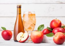 Bottle and glass of homemade organic apple cider with fresh apples in box on wooden background Stock Photo