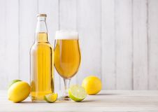 Bottle and glass of lager beer with lemon and lime. On light wooden background royalty free stock photos
