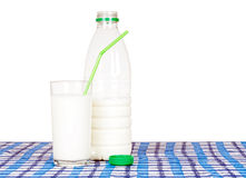Bottle and glass of milk, on check tablecloth. Green straw. Stock Images