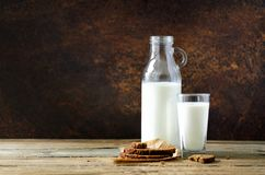Bottle and glass of milk, whole wheat bread on wooden table, dark background. Sunny morning, copy space Stock Photo