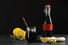 Bottle and glass with natural charcoal lemonade on table. Against dark background stock image