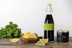 Bottle and glass with natural charcoal lemonade on table. Against light background royalty free stock photography