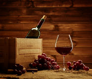 Bottle, glass and red grape on a wooden table Royalty Free Stock Photography