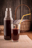Bottle and glass of red juice on a wooden table Royalty Free Stock Photo