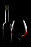 Bottle and glass of red wine. Over black background. Copy space on top Royalty Free Stock Photo
