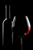 Bottle and glass of red wine. Over black background Stock Images