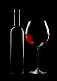 Bottle and glass of red wine. Over black background Stock Image
