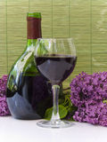 Bottle and glass of red wine. With lilac flowers-outdoorsy setting Stock Images