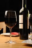 Bottle and Glass of Red Wine. Bottle and a glass of red Wine on a wooden restaurant table royalty free stock images