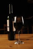 Bottle and Glass of Red Wine. Bottle and a glass of red Wine on a wooden restaurant table stock photo