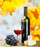 Bottle, glass of red wine and assorted cheeses Royalty Free Stock Photography