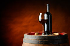 Bottle and glass of red wine. Red wine in a glass and bottle on a barrel Royalty Free Stock Image