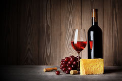 Bottle and glass of red wine with cheese grapes royalty free stock photo