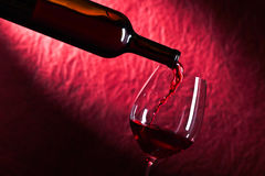 Bottle and glass of red wine on a dark  background Stock Photos