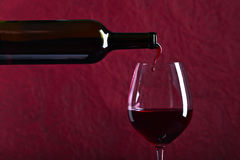 Bottle and glass of red wine on a dark  background Royalty Free Stock Images