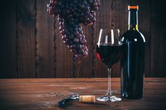 Wine. Bottle and glass of red wine, grape and cork on wooden background Stock Images
