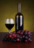 Bottle and glass of red wine with grapes Stock Images