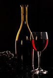 Bottle and glass of wine grapes on black background Stock Images
